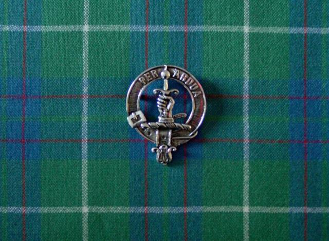 Silberne Anstecknadel eines schottischen Clans mit Wappen liegt auf Karostoff