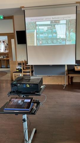 ein Beamer zeigt eine Präsentation von einem Laptop auf eine Leinwand in einem Seminarraum