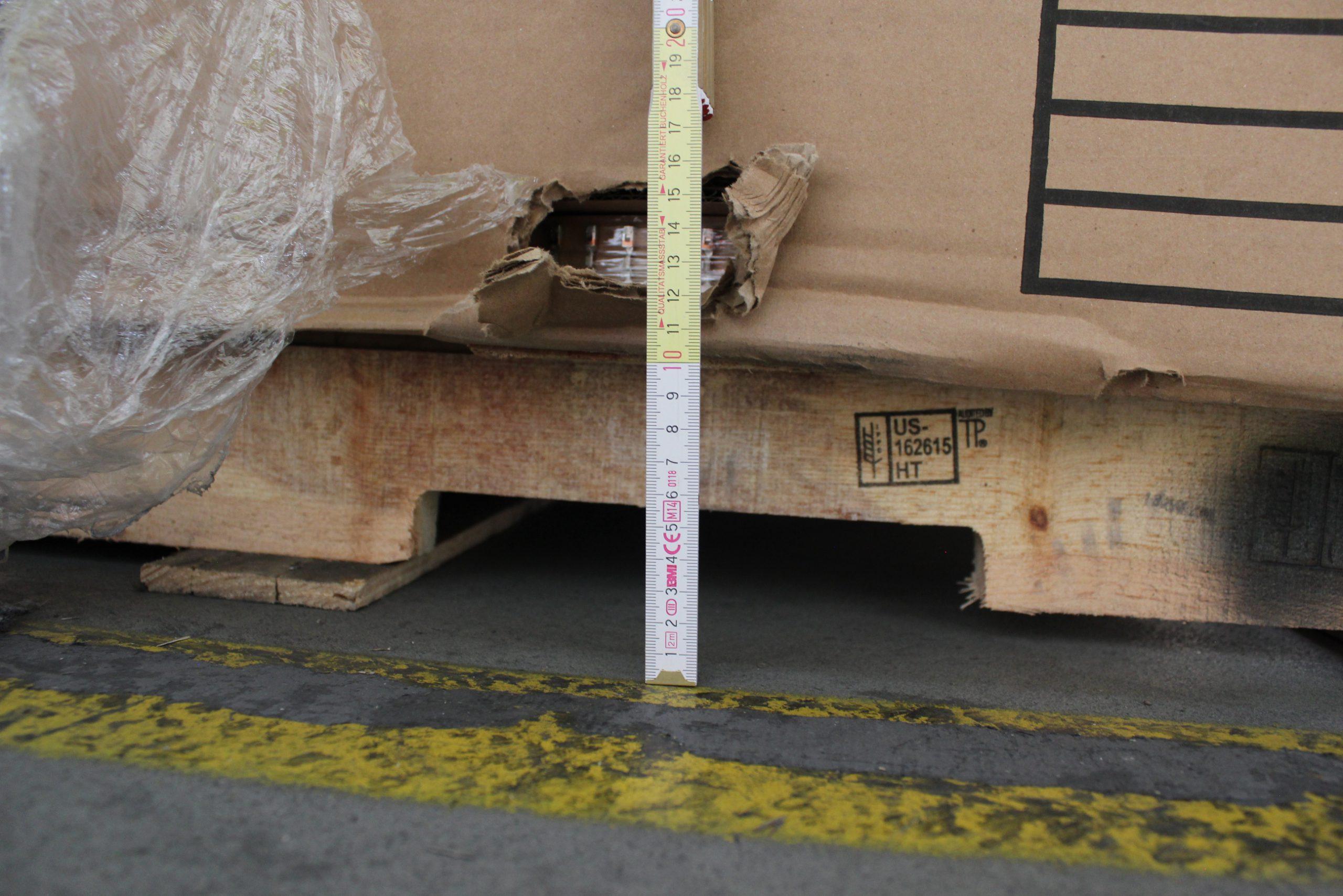 ein Karton auf einer Palette ist durch eine Staplergabel beschädigt