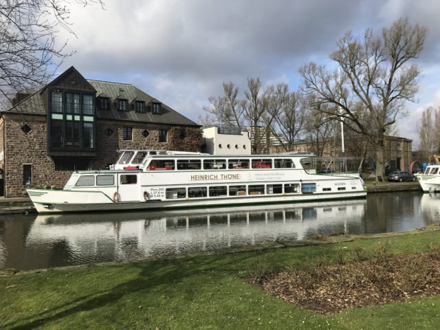 ein weißes Personenschiff auf der Ruhr und im Hintergrund die alte modernisierte Schleuse